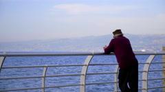 Man staring at the sea on the marina sidewalk, Lebanon - stock footage
