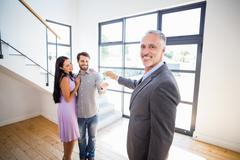 Real-estate agent giving keys to couple - stock photo