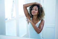 Young woman applying powder on her underarms Stock Photos