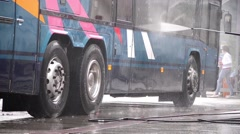 Man washed with pressurized water a bus in the yard of a wash Stock Footage