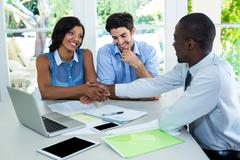 Happy couple shaking hands with real estate agent - stock photo