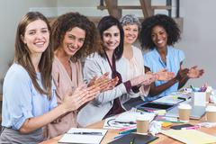 Group of interior designers applauding in office Stock Photos