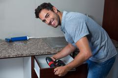 Portrait of happy man using cordless hand drill - stock photo
