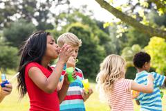 Children blowing bubbles wand in the park Stock Photos