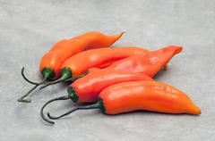 Aji amarillo hot chili peppers on stone background - stock photo