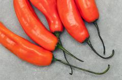 Group of Aji amarillo hot chili peppers on stone background - stock photo