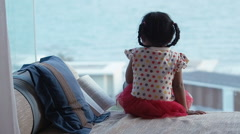 Little girl sitting and open book in sea scenery background. Arkistovideo