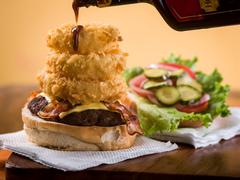 Bacon Cheeseburger with Stack of Onion Rings Stock Photos