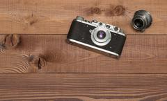 vintage camera with lens on the wooden background - stock photo