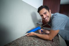 Portrait of happy man using pest control injection - stock photo