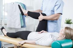 Chiropractor stretching female leg Stock Photos