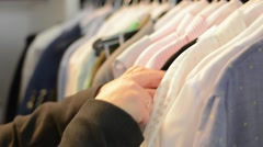 Young Woman Looks Through Clothes Hanging On A Rack Stock Footage