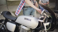 Biker put ignition key into grey motorcycle. Summer sunny day. Camera hang on Stock Footage