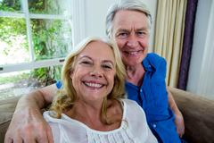 Smiling senior couple sitting in living room at home Stock Photos