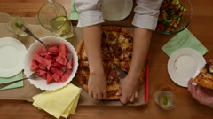 Girl hands take second piece of pizza, small home party, desk view Stock Footage