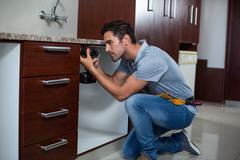 Full length of man using cordless hand drill Stock Photos