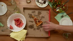 Man hand take last piece of pizza, top shot, small wooden table Stock Footage
