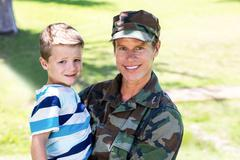 Happy soldier reunited with his son - stock photo