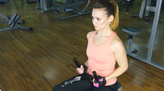 Young woman flexing muscles on gym machine Stock Footage