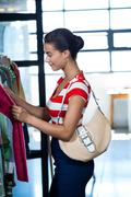 Woman selecting an apparel while shopping for clothes - stock photo