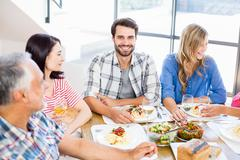 Man sitting with friends at dinning table - stock photo
