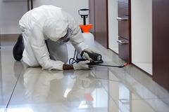 Pest control man spraying pesticide under the cabinet - stock photo