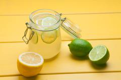Lemonade with ice, lemon and lime in a jar on a yellow wooden background. Stock Photos