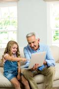 Girl pointing at laptop while sitting with granddad Stock Photos