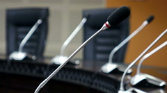 Dolly shot of microphones in modern conference room Stock Footage
