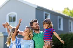 Parents carrying children with arms raised Stock Photos