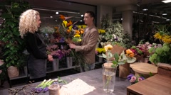 Young man buys a bouquet at flower shop - stock footage