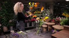 Beautiful woman florist making a bouquet at flower shop - stock footage
