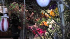 Florist consultation - man chooses the flowers for a bouquet in shop - stock footage