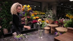 Beautiful woman florist making a bouquet at flower shop - stock footage