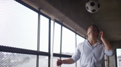 Young man doing headers with a football in urban environment, in slow motion - stock footage