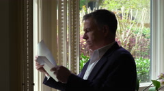 Man reading some mail standing by a window to his house 4k Stock Footage