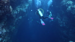 Group of scuba divers swimming on deep water wall and cavern tunnel in Palau Stock Footage