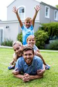 Boy with arms raised with family in yard - stock photo