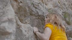 A female rock climber climbs up a rock Stock Footage