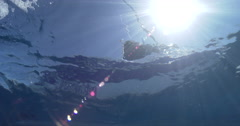Ocean scenery looking up at boat and sunball, shot breaks the surface to show Stock Footage