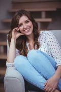 Portrait of beautiful woman sitting on sofa Stock Photos