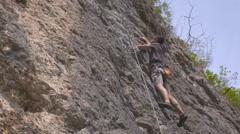 A male rock climber climbs up a rock Stock Footage