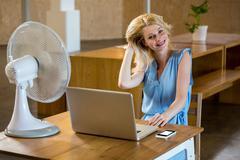 Woman enjoying a breeze while using laptop - stock photo