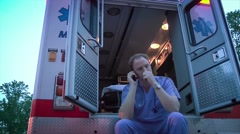 Doctor Sitting In Back of Ambulance Talking On Cell Phone - stock footage