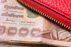 Red leather wallet with thai banknote money, close up Stock Photos