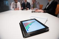 close up of touchpad with analytics documents at business meeting - stock photo