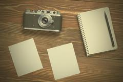 Travel, vacation concept. Camera, notepad, pen and photography on office wooden Stock Photos