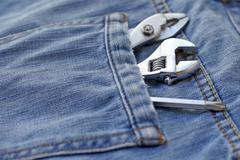 several tools in workers pocket jeans - stock photo
