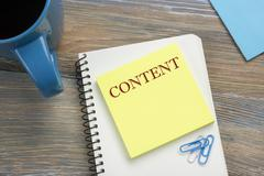 Content, online concept. Notepad with message and coffee cup. Office supplies on Stock Photos