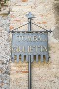 "Plaque ""Juliet's tomb"" at the entrance of the homonymous tomb in Verona. Stock Photos"